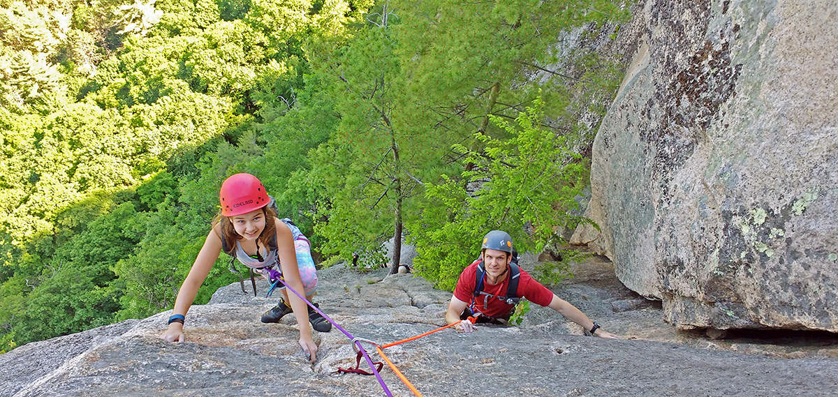 Girl and guide climbing on rock climbing route. Upper Refuse, Cathedral Ledge, NH.